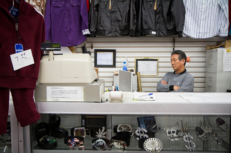 Man Ku Baek, a Korean business owner in downtown Nogale, Ariz., watches a Korean television show behind his cash register at Susan's Fashion. (Photo by Josh Morgan)